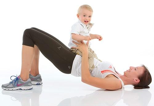 Delafit Fitness-Mutter mit lachendem Kind auf ihr